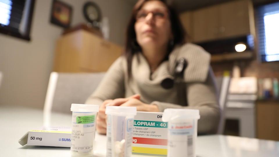 Nancy Laporte, victime d'agressions sexuelles et atteinte de fibromyalgie, pose derrière des médicaments.