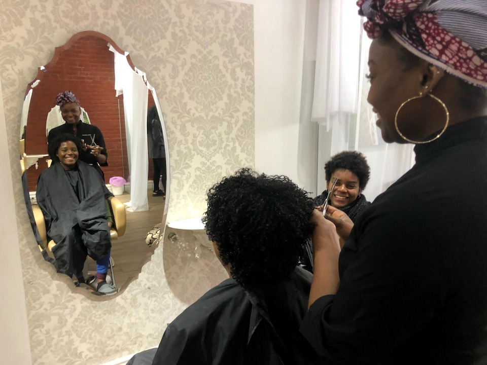 Mia redécouvre ses cheveux sans produits défrisants sous les yeux de sa soeur et de la coiffeuse Danielle.