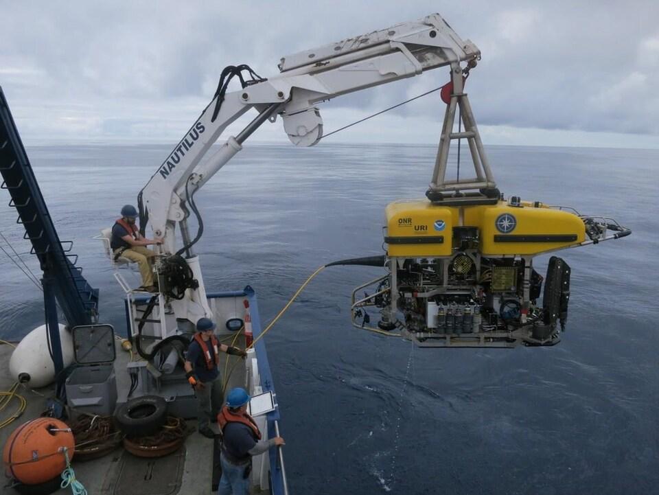 un homme avec casque et veste de sauvetage contrôlen une grue qui descend dans la mer un véhicule sous-marin. Deux autres hommes regardent, on voit la mer à perte de vue.