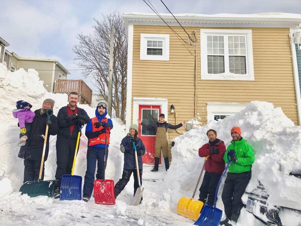 Groupe de personnes avec des pelles à neige devant une maison.