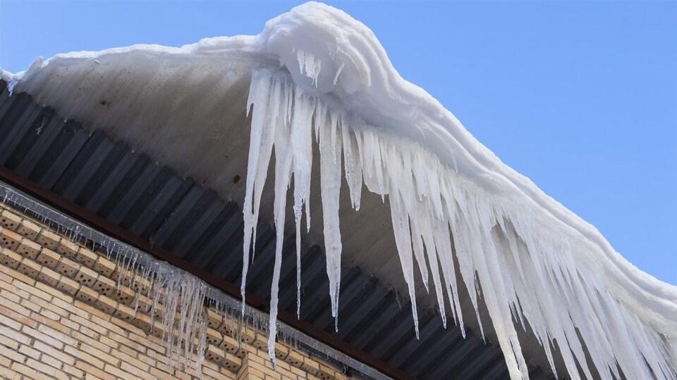 De la neige et de la glace sur le point de tomber d'un toit après un épisode de redoux.