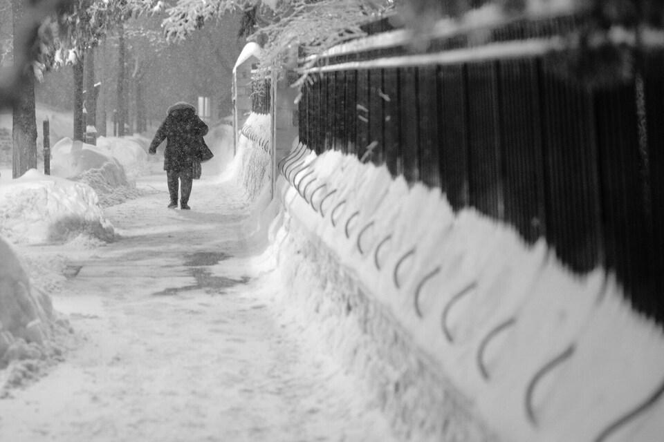 Bien que la neige tombait toujours à gros flocons sur la rue Saint-Jean, les trottoirs étaient bien déneigés.