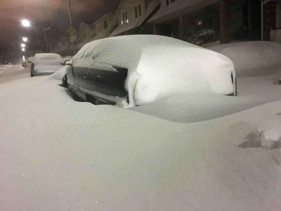 Photo de voitures recouvertes de neige dans une rue