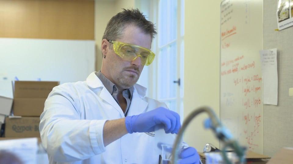 Il collecte un échantillon d'eau dans son laboratoire.