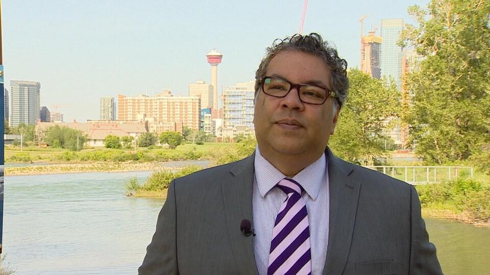 Le maire se tient devant la rivière Bow.