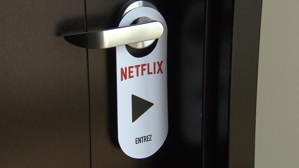 Un carton de Netflix est accroché sur une poignée de porte.