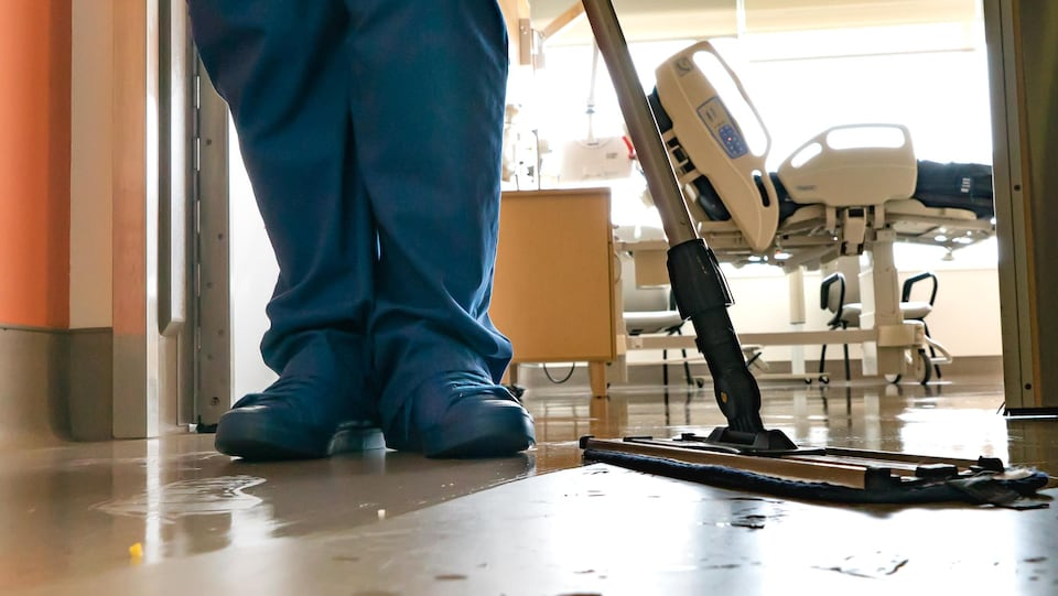On voit en gros plan les chaussures de l'employée et la vadrouille qui est en train d'être passée sur le plancher. En arrière-plan, on voit le lit dans la chambre d'hôpital et l'équipement.