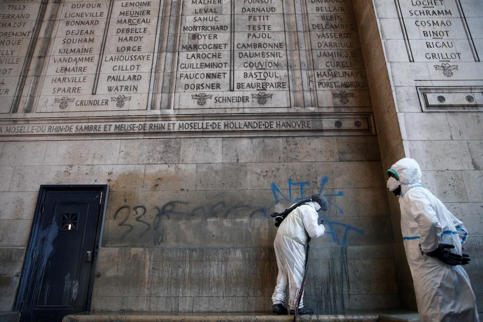 Des hommes en blouses blanches tentent de nettoyer des graffitis sur un bâtiment de pierre.