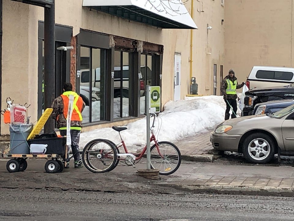Deux personnes portant des vestes de sécurité près d'un vélo auquel est accroché un chariot.