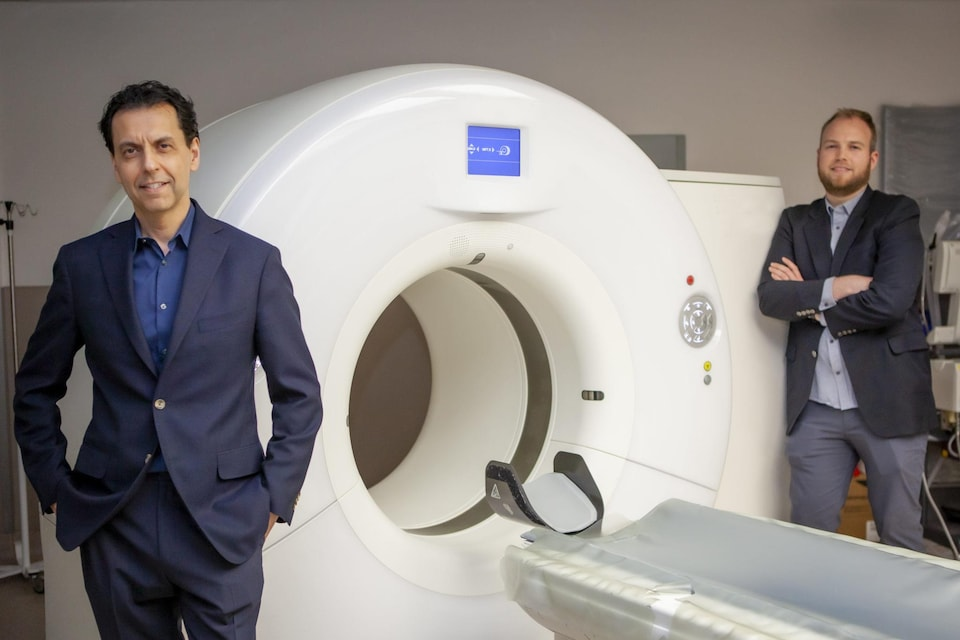 Le Dr Savvas Nicolaou et le Dr William Parker sont debout dans une salle d'imagerie médicale, à côté d'un appareil.