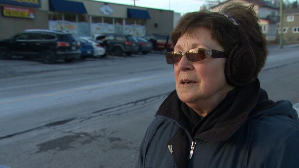 Nicole Bertrand répond aux questions d'une journaliste dans la rue.