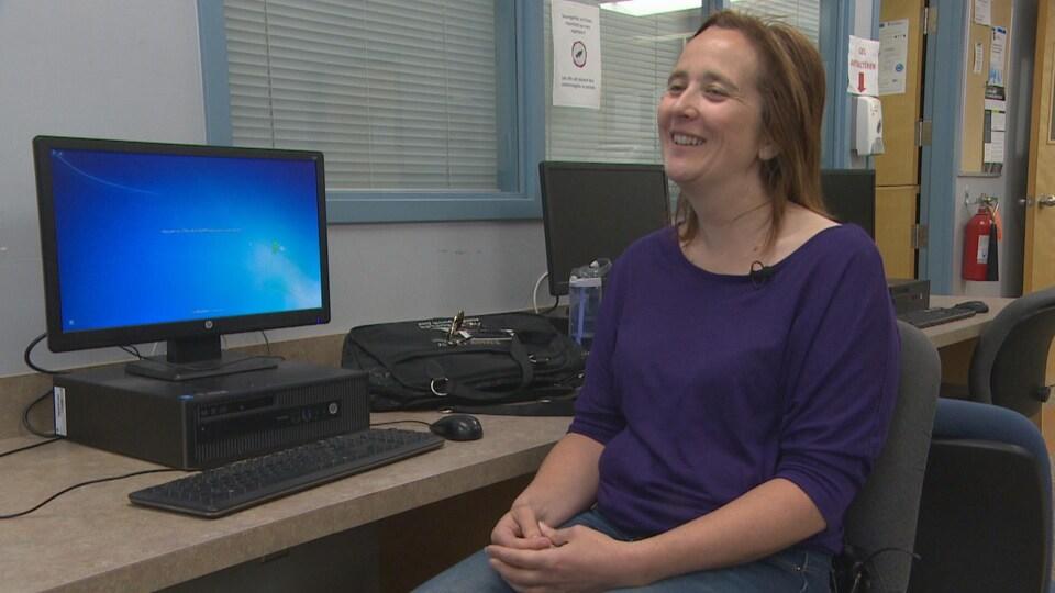 Une femme assise sourit en regardant la caméra.