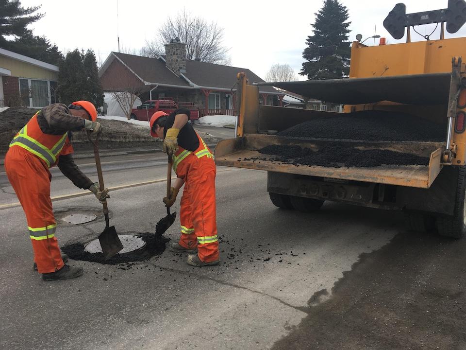 Des travailleurs réparent la chaussée