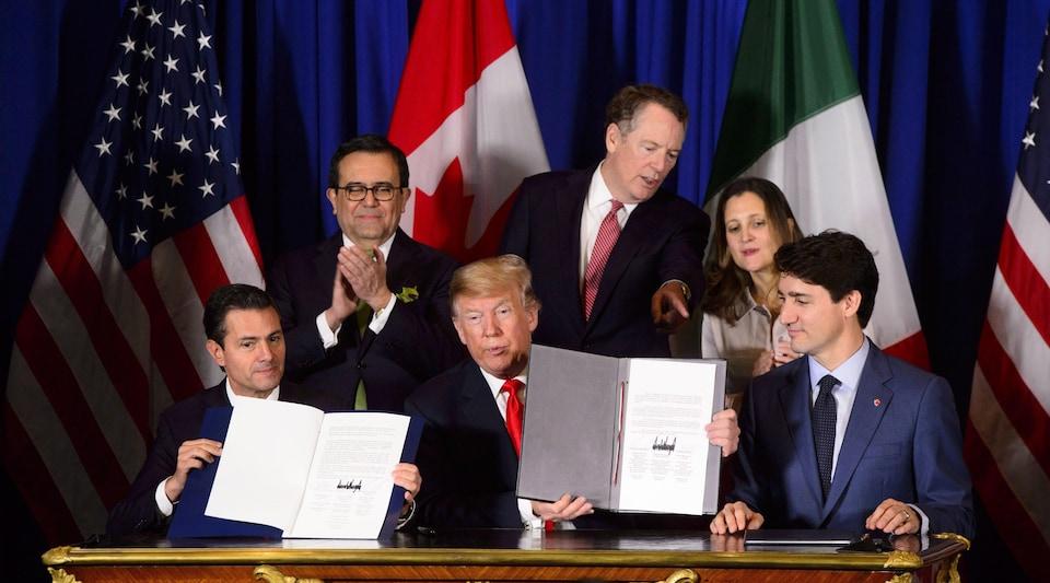 Une image montre Justin Trudeau à une table aux côtés des deux autres dirigeants.
