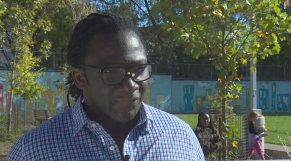 Nigel Barriffe, président du groupe Urban Alliance on Race Relations porte une chemise à carreaux et des lunettes