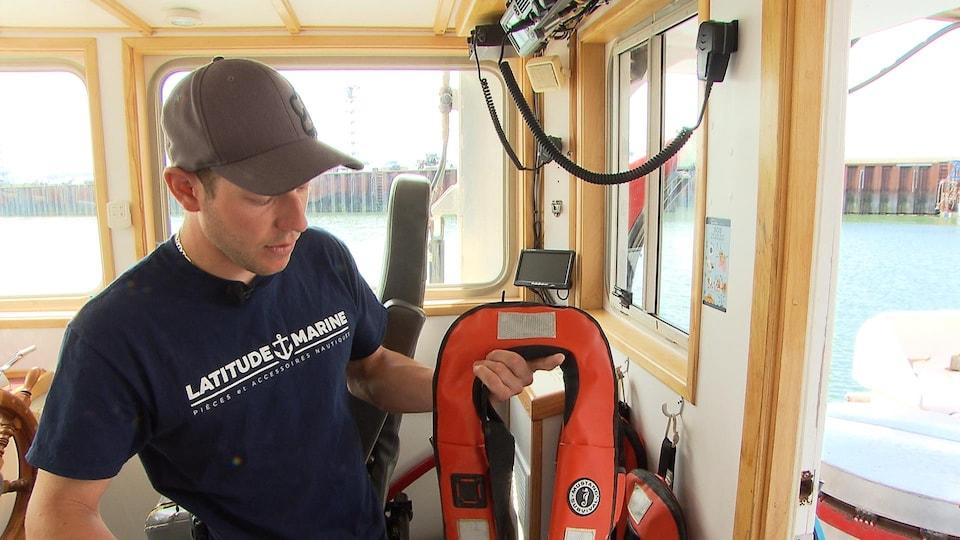 Le pêcheur Marc Doucet montre les nouveaux vêtements de flottaison à déclenchement automatique portés sur le Bicois.