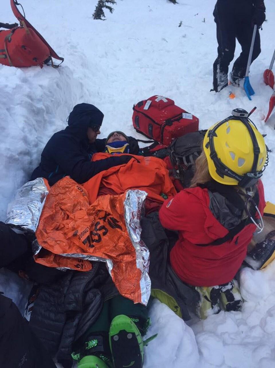 Photo de la victime entourée de son ami et d'une secouriste.