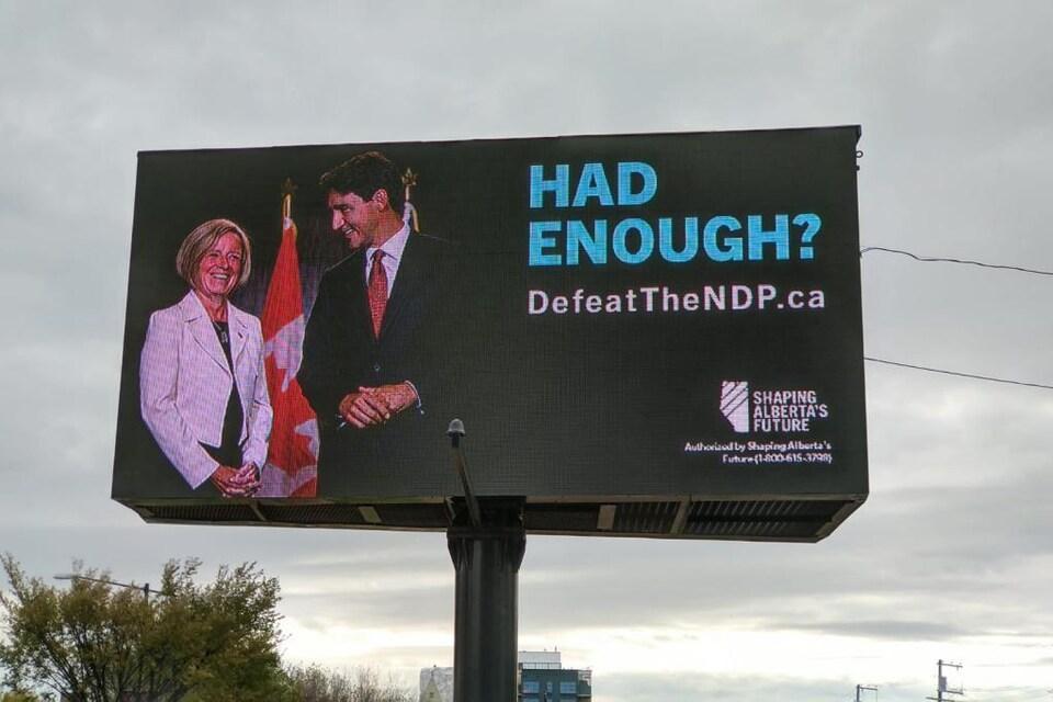 Une pancarte montre Rachel Notley et Justin Trudeau tout sourire. Il est inscrit en anglais : «Had Enough?».