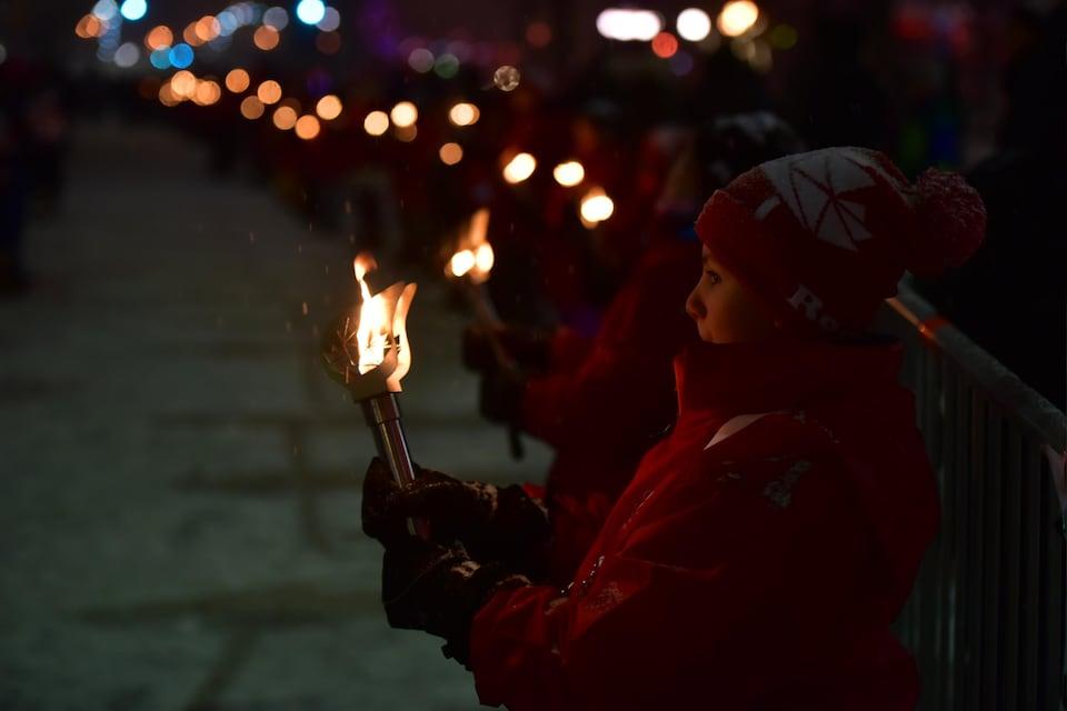 Un jeune porte un flambeau pour le 150e.