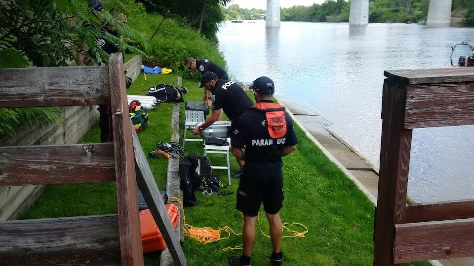 Deux ambulanciers et un policier organisent leur équipement près de la rivière Rideau.