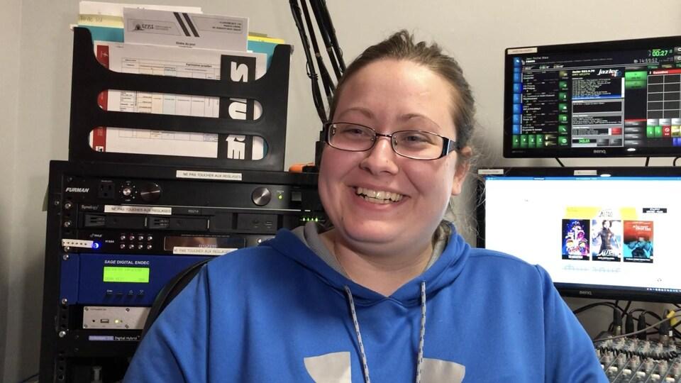 Une femme portant des lunettes sourit devant des écrans d'ordinateur et de l'équipement électronique.