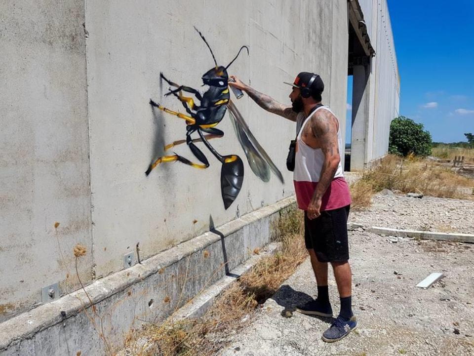 Un homme peint une guêpe sur un mur.
