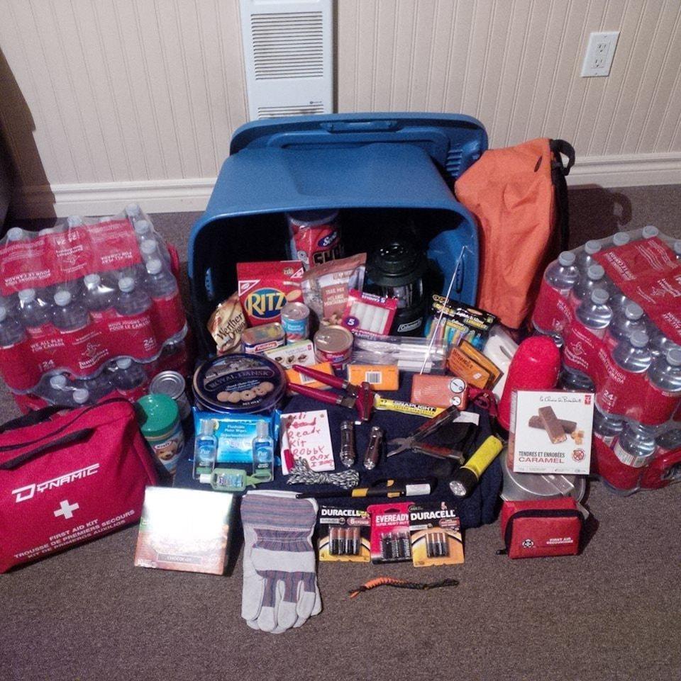 Des bouteilles d'eau, de la nourriture et des piles étalés sur le sol