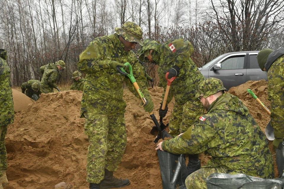 Un groupe de soldats remplit des sacs avec du sable
