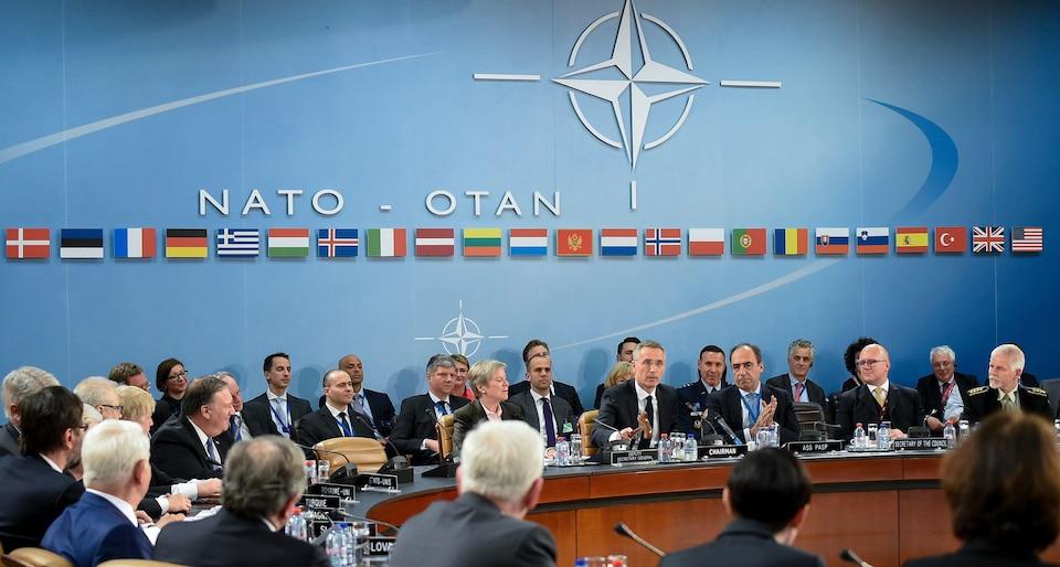 Plusieurs personnes sont assises et discutent entre elles avec, sur le mur du fond, le logo de l'OTAN et les drapeaux de tous les pays membres.