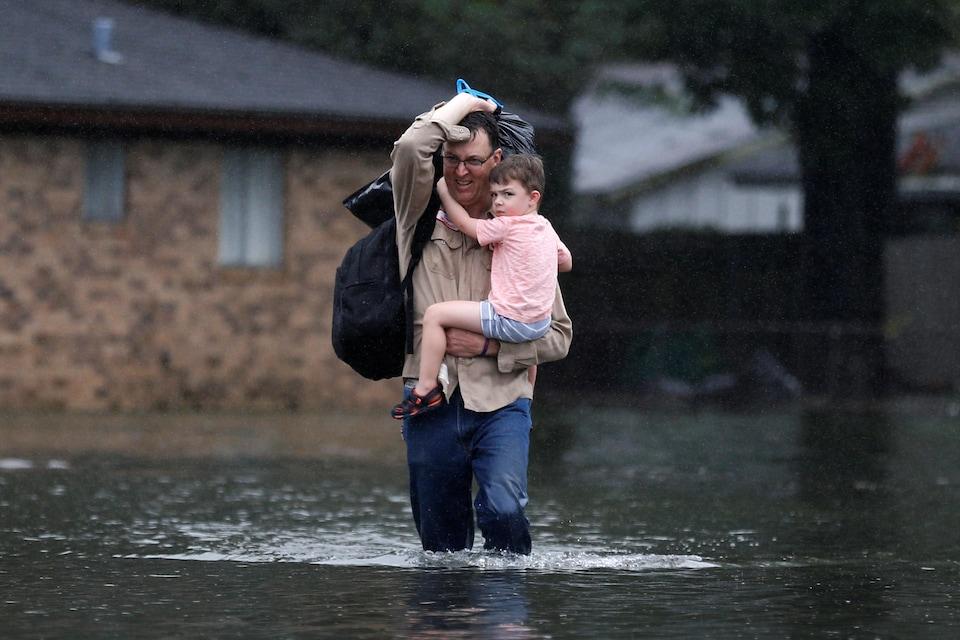 David Michaelis transporte son petit-fils Teddy, âgé de trois ans, dans les rues inondées d'Orange, au Texas.