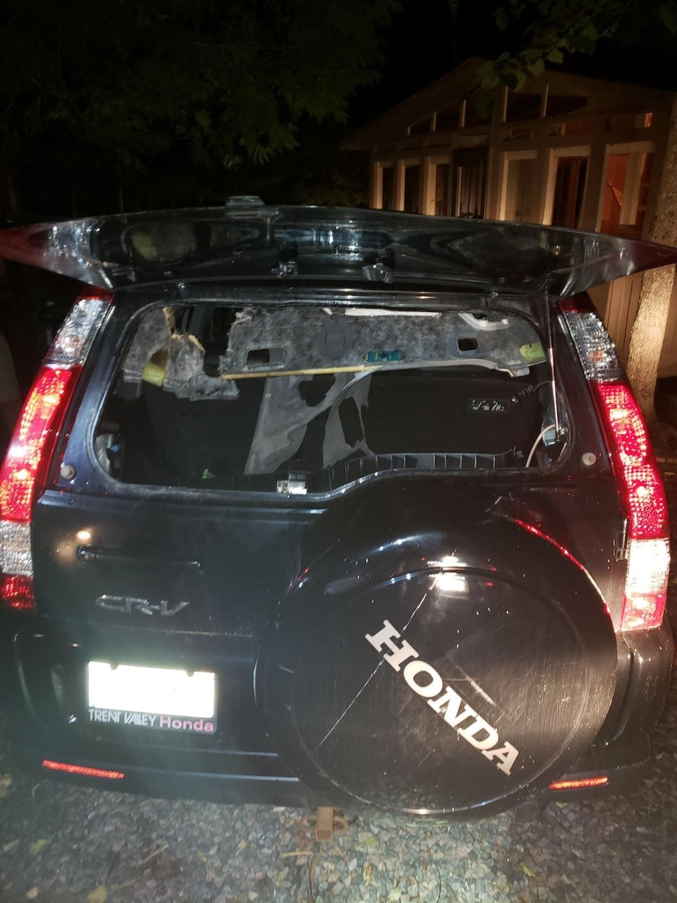 Vue arrière du véhicule avec une fenêtre cassée.