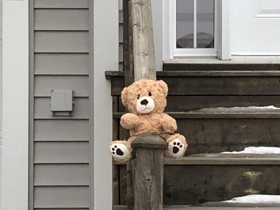 Un ourson en peluche sur une rampe d'escalier devant une maison d'Halifax.