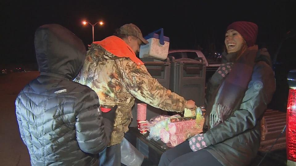 Trois personnes distribuent du café sur le quai.