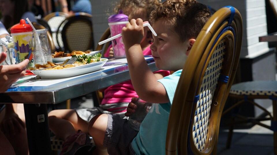 Un enfant tient une paille de plastique dans sa main à la table d'un restaurant de Québec