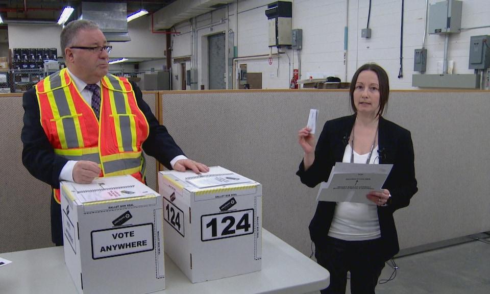 Pamela Renwick, porte-parole d'Élections Alberta, dans un entrepôt à côté de deux urnes.