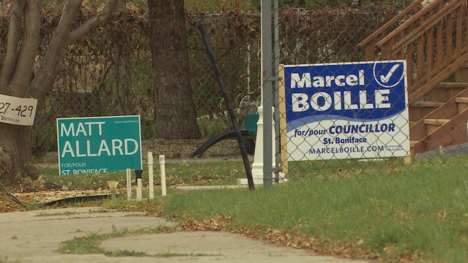 Au fond, une pancarte verte pour le candidat Matt Allard, et au premier plan, une pancarte bleue pour Marcel Boille.