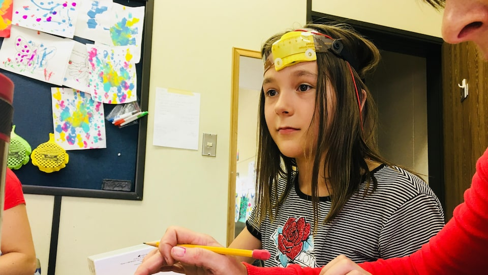 Fillette portant un casque avec des électrodes et des fils.