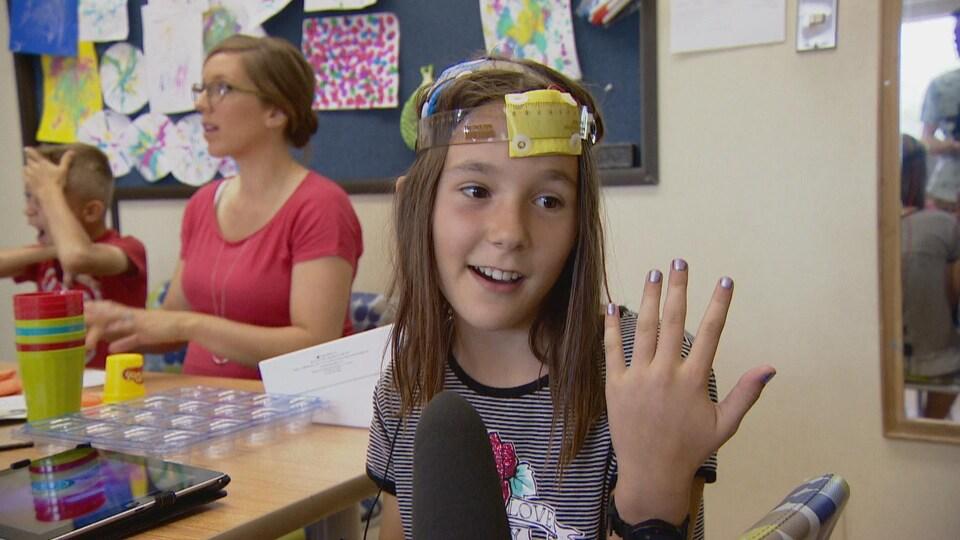 Fillette montrant sa main gauche, dont les ongles sont vernis.