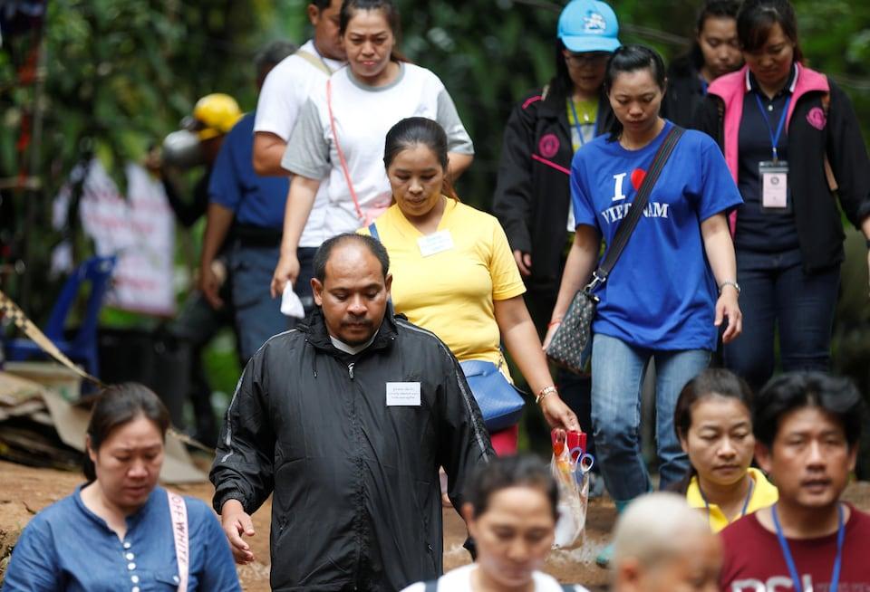 Des proches des jeunes piégés dans une grotte et des moines bouddhistes sortent du complexe de la grotte Tham Luang, où 12 jeunes et leur entraîneur sont piégés depuis 14 jours.