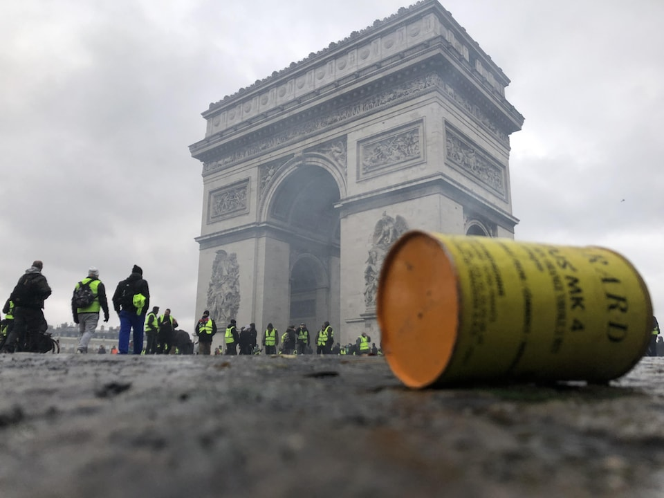 Une canette de gaz lacrymogène au sol est visible à l'avant-plan devant des manifestants portant des gilets jaunes debout devant l'Arc de triomphe, à Paris.