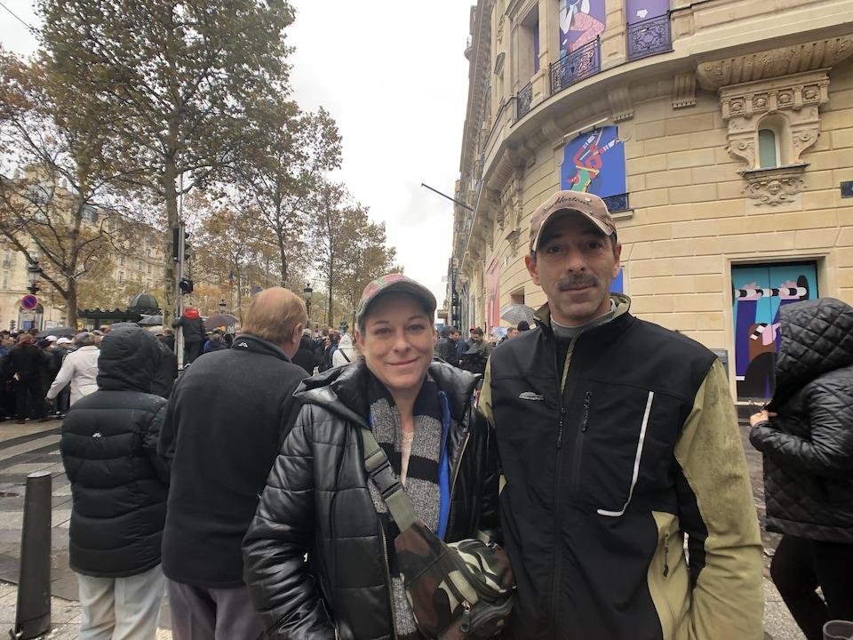 Un homme et une femme posent pour la caméra devant un immeuble dans une rue de Paris.