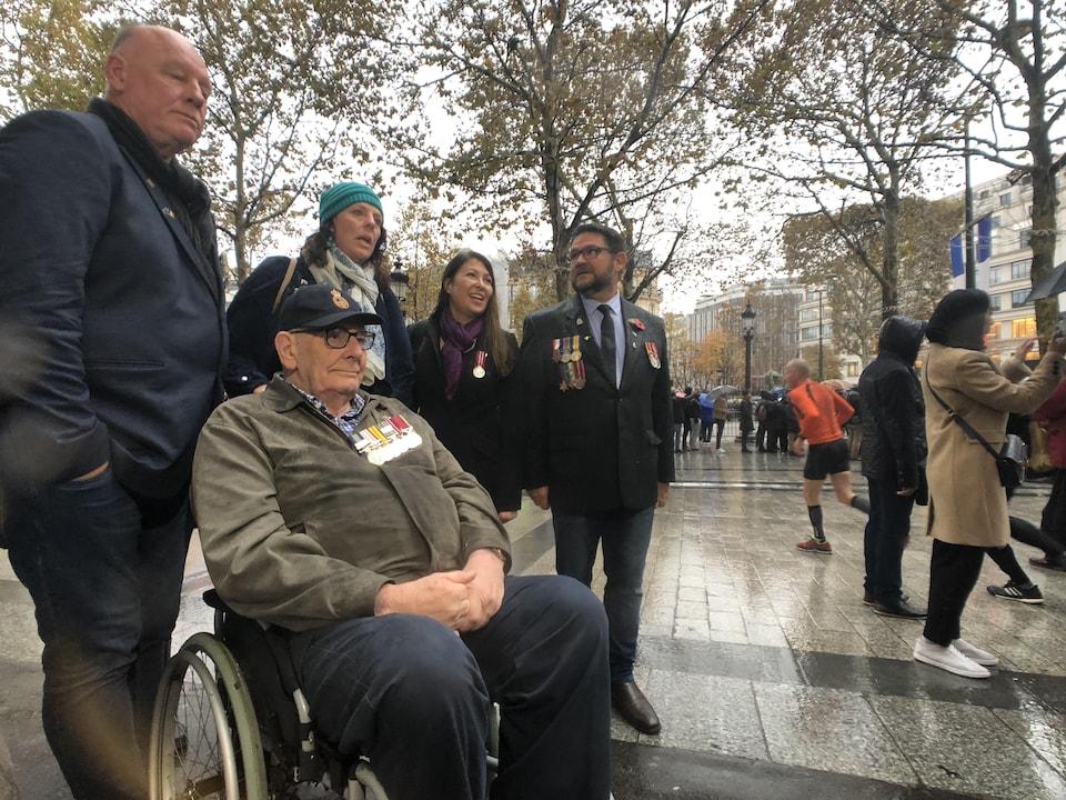 Un homme en fauteuil roulant est entouré de deux hommes et de deux femmes dont certains portent des médailles militaires sur leur manteau.