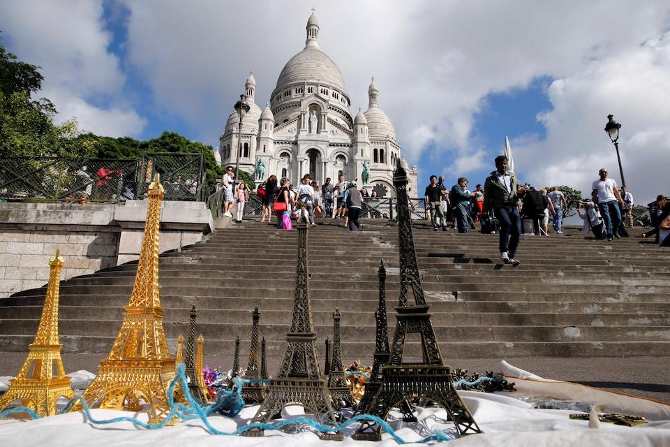 La basilique du Sacré-Coeur de Montmartre, devant laquelle des vendeurs ont étalé des modèles réduits de la tour Eiffel.