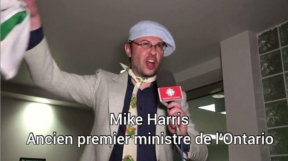 Éric Robitaille déguisé en Mike Harris, avec un drapeau franco-ontarien à la main.