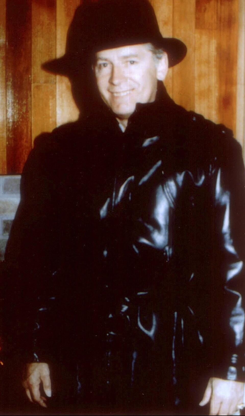 Le gangster américain pose dans un imperméable de cuir noir et un chapeau de feutre noir sur la tête.