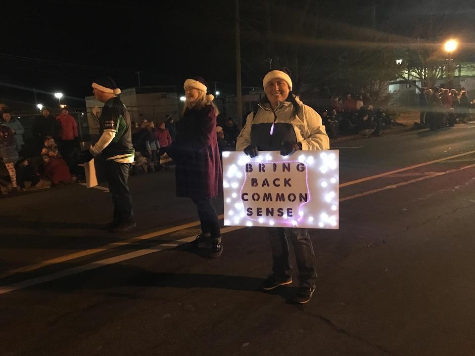 Des gens souriants coiffés de tuques de Noël défilent avec des pancartes affichant des slogans