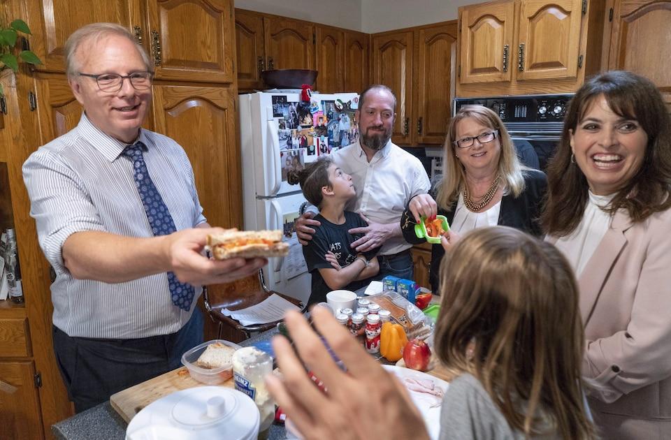 Le chef du PQ, Jean-François Lisée, le candidat  Constantin Fortier, les députées Carole Poirier et Véronique Hivon dans une cuisine pour une conférence de presse portant sur les lunchs d'écoliers