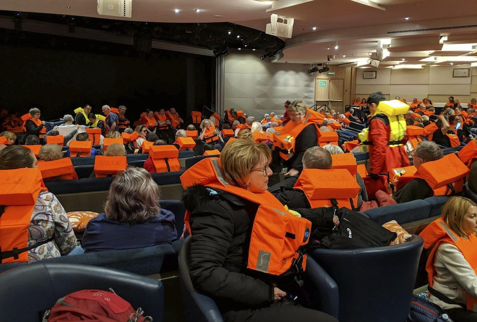 Une foule de passagers attendent, assis, une veste de sauvetage au cou.