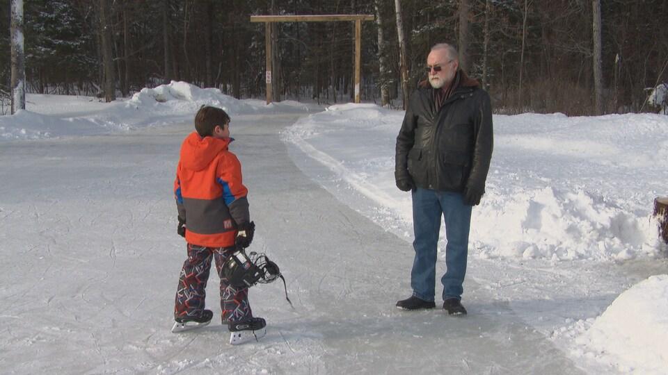 Un enfant patine sur un sentier glacé dans la forêt.