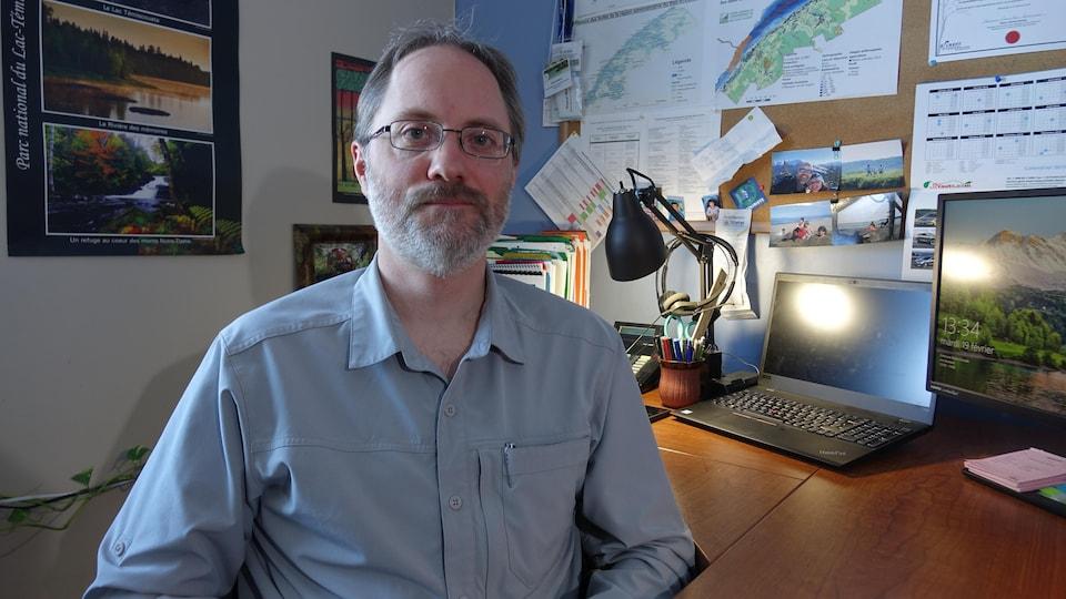 Patrick Morin est assis à son bureau.